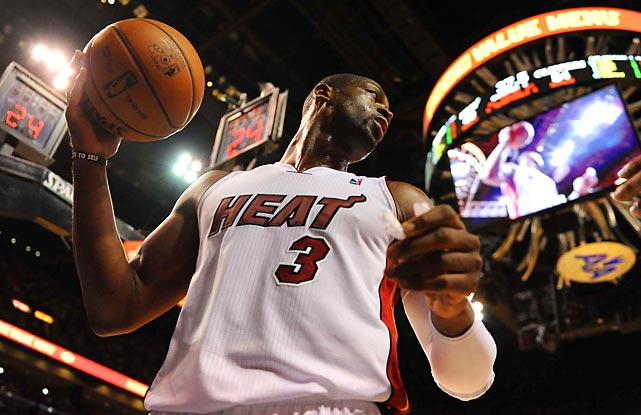 Dwyane Wade looks up during a game as his image is broadcast on the jumbotron.