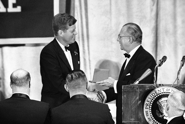 President John F. Kennedy receives a gold medal for his contribution to sports and football from Chester J. Laroche, President of the National Football Foundation, at the annual awards banquet held on Dec. 5, 1961 in New York.