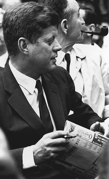 President John F. Kennedy sits in the stands, a scorecard in his hand, as he watches a Washington Senators baseball game in 1962 at Griffith Stadium in Washington, D.C.