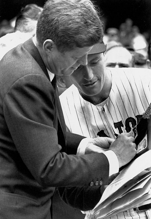 President John F. Kennedy signs an autograph for a member of the Washington Senators prior to their opening day baseball game game against the Detroit Tigers on April 9, 1962 at Griffith Stadium in Washington, D.C.