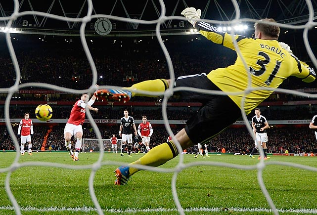 Olivier Giroud shoots past Southampton goalkeeper Artur Boruc to score the 2nd Arsenal goal during the match at Emirates Stadium.
