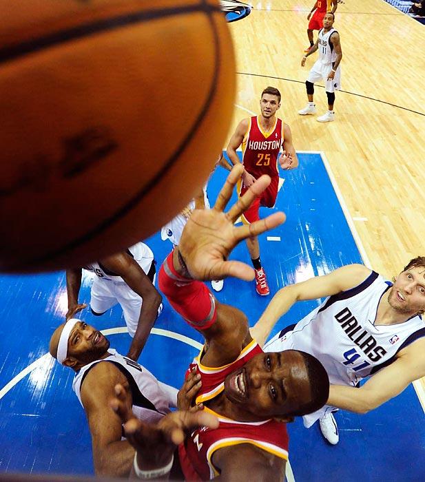 Rockets center Dwight Howard fights off Mavericks guard Vince Carter for a rebound.