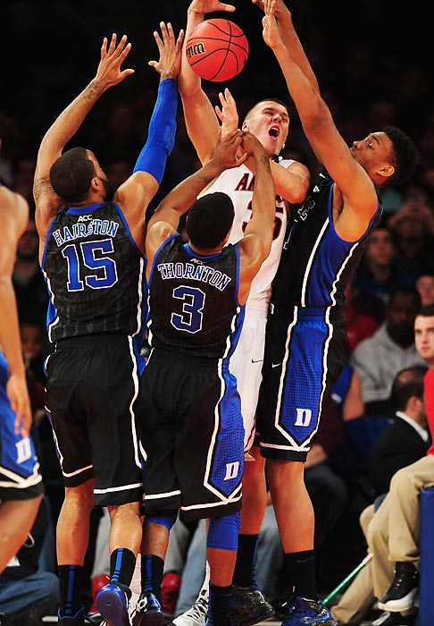 Duke players swarm Arizona center Kaleb Tarczewski during the championships game of the NIT Season Tip-Off at Madison Square Garden. The No. 4 Wildcats held off the No. 6 Blue Devils 72-66, led by a balanced offensive attack that put five Arizona players into double figures.