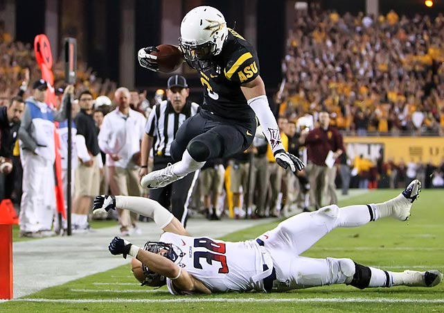 Arizona State running back D.J. Foster hurdles Arizona safety Jared Tevis for one of his two touchdowns in the Territorial Cup on Saturday. The No. 13 Sun Devils dismantled the Wildcats 58-21, earning the right to host the Pac-12 Championship Game this weekend.