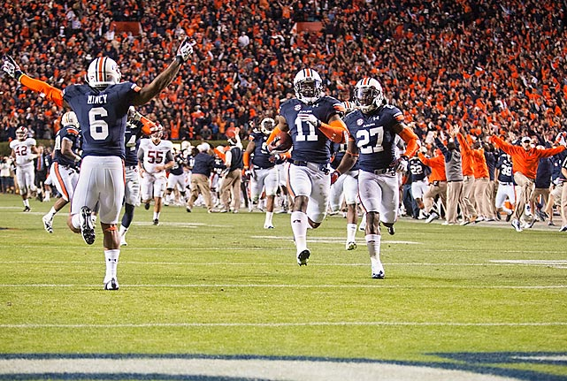 Surrounded by fellow Tigers, Auburn's Chris Davis finishes his end-zone-to-end-zone dash to win the Iron Bowl over Alabama and send a sold-out Jordan-Hare Stadium into a frenzy. The touchdown gave Auburn a 34-28 victory over the previously undefeated Crimson Tide, who attempted a game-winning 57-yard field goal to begin the historic finish.