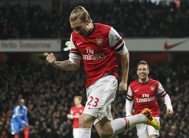 Nicklas Bendtner celebrates his opening goal as Arsenal defeated Hull City 2-0 on Wednesday to retain its four-point lead atop the Premier League.