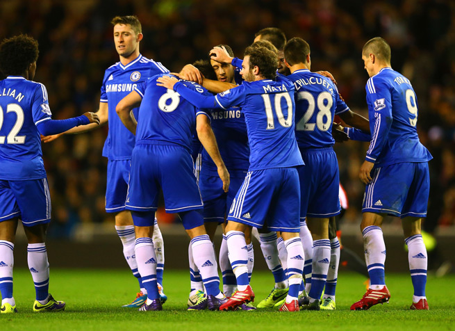 Chelsea players mob Eden Hazard after one of his two goals in the Blues' 4-3 win over Sunderland Wednesday.