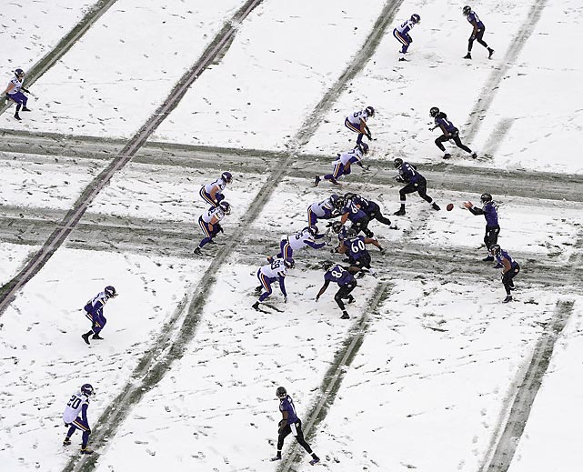 Ravens quarterback Joe Flacco takes the snap on a snowy day in Baltimore. The Raven prevailed 29-26 in a wild finish against the Minnesota Vikings that featured five lead changes in the final 2:06.