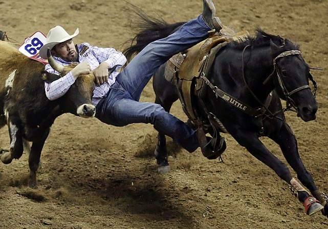 K.C. Jones grabs horns in the steer-wrestling competition during the first go-round of the National Finals Rodeo on Thursday in Las Vegas. Trevor Brazil set a record with his 19th world championship at the rodeo.