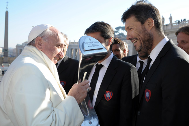 Pope Francis examines his own Argentina league championship replica trophy, which was presented to him by his favorite club, title-winning San Lorenzo.