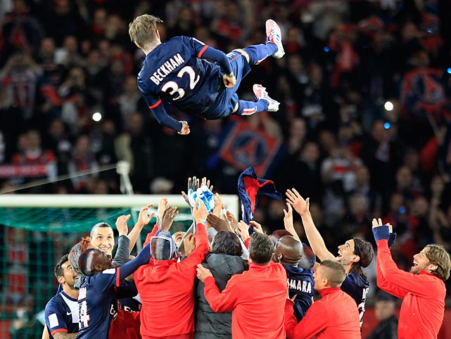 Paris Saint Germain's midfielder David Beckham is thrown in the air by his teammate at the end of their French League One soccer match against Brest, at the Parc des Princes stadium in Paris.