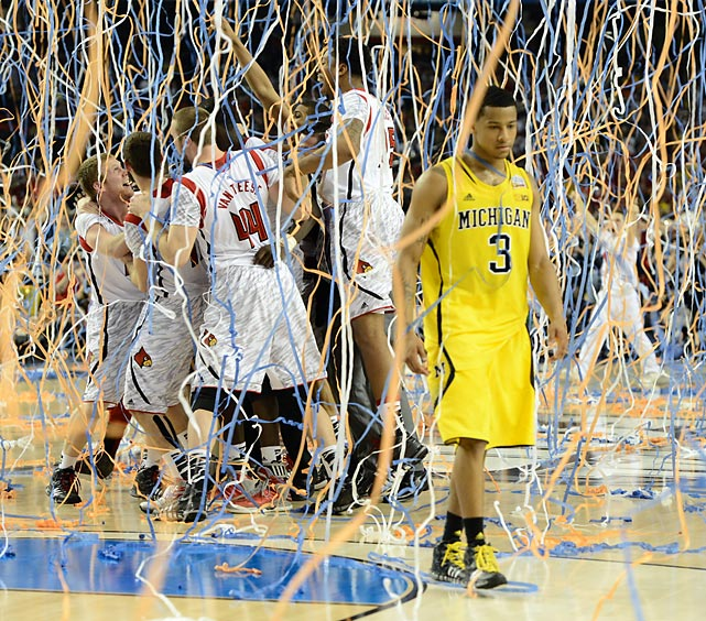 Louisville celebrates their Final Four victory as Michigan's Trey Burke walks off court.
