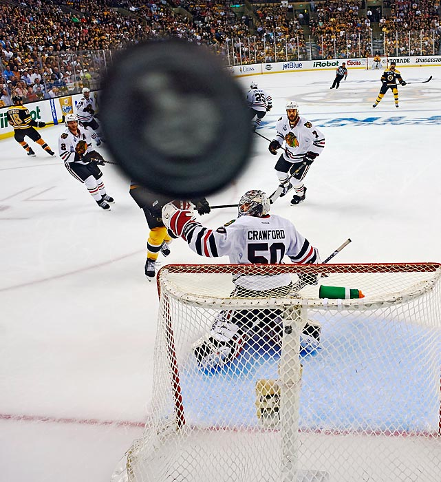 The puck flies over Chicago Blackhawks goalie Corey Crawford in game 3 of the NHL Finals against the Bruins.