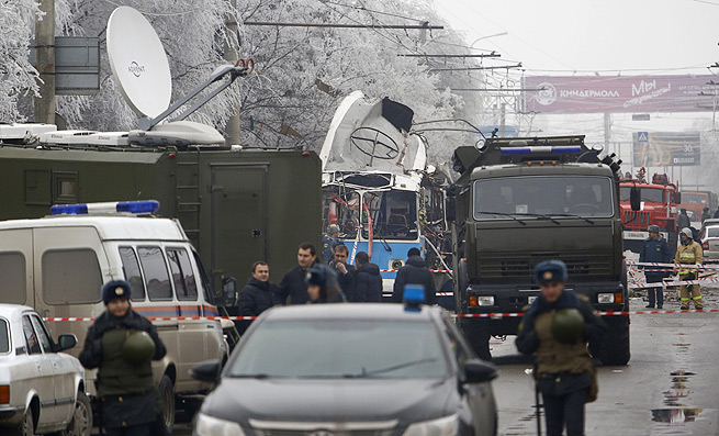 Security vehicles surround a trolleybus after a suicide bombing killed at least 10.