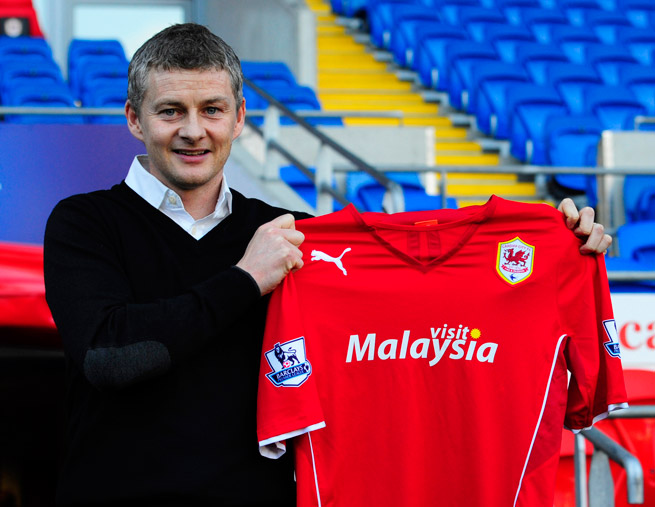 New Cardiff City manager Ole Gunnar Solskjaer poses with his team's uniform after being hired on Thursday.