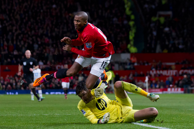 Manchester United's Ashley Young, shown above colliding with Tottenham goalkeeper Hugo Lloris on New Year's Day, will miss an undetermined amount of time with a shoulder injury.