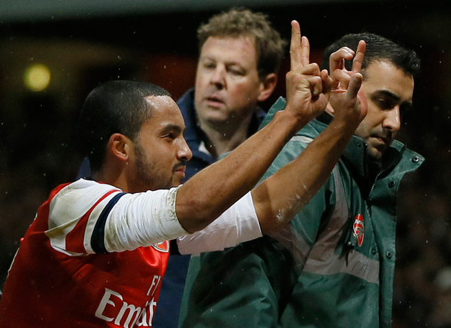 Arsenal star Theo Walcott mocks Tottenham fans by hand-gesturing the score as he is stretchered off the field in Saturday's FA Cup victory.