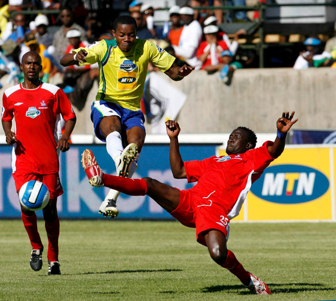 "Patrick Apataki goes airborne for the Mamelodi Sundowns in 2007, donning the yellow and blue uniforms introduced by owner Zola Mahobe, who dubbed his team ""The Brazilians."""