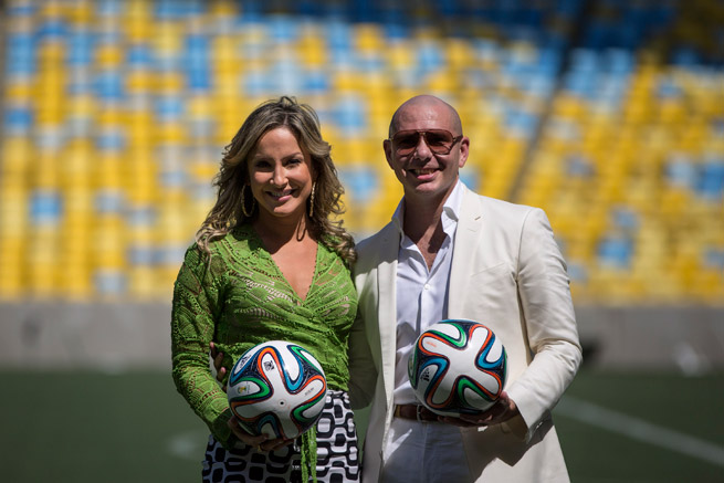 Brazilian recording artist Claudia Leitte and rapper Pitbull pose on the field at Estadio do Marcana following the announcement that they will collaborate with Jennifer Lopez for the official World Cup song.