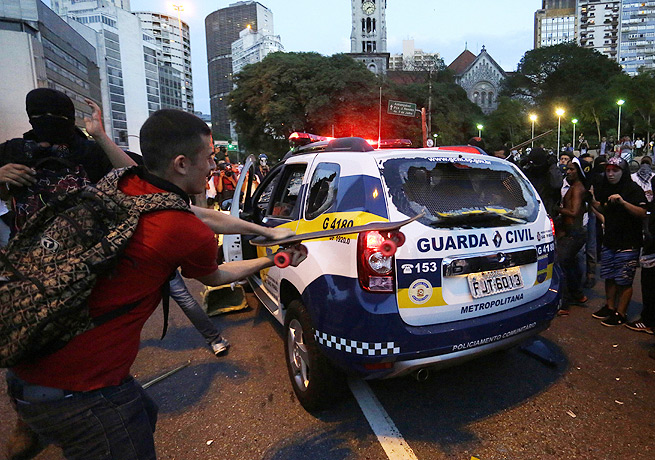 Protesters attacked an empty police car while demonstrating against the World Cup in Sao Paulo.