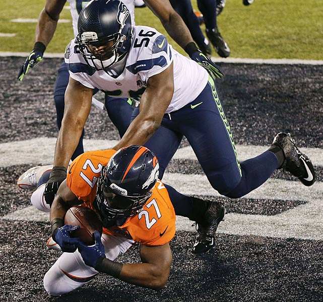 Knowshon Moreno gets to the ball ahead of Seattle Seahawks defensive end Cliff Avril. The points were the fastest scored in Super Bowl history.