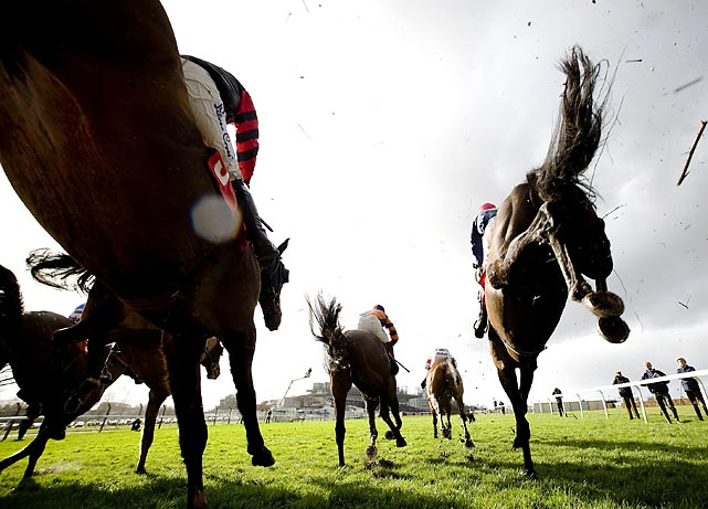 Horses in the Belfred 'Double Delight' Novices' Limited Handicap Steeple Chase leap over a face during competition at Sandown Racecourse in Esher, England.