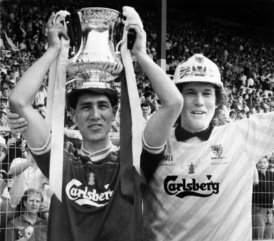 Wimbledon's Lawrie Sanchez holds the FA Cup as captain and goalkeeper David Beasant acknowledges the fans after defeating Liverpool 1-0 in the 1988 FA Cup final.