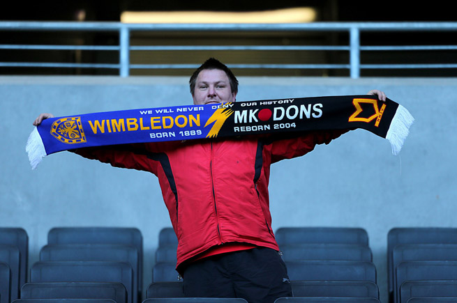 A fan holds a scarf commemorating Wimbledon's FA Cup match against MK Dons in the 2012 FA Cup, an emotional day for Wimbledon supporters confronting their past and present.