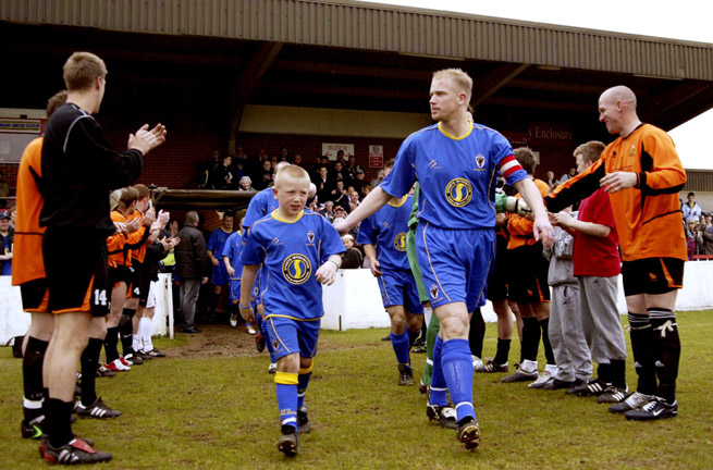AFC Wimbledon captain Steve Butler leads the club through a champions guard of honor given by Division One opponent Cray in 2005.