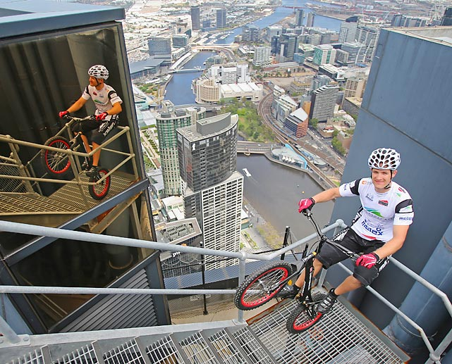 The Polish extreme cyclist (indeed) broke his own Guinness World Record by bucking and jumping up 2,919 steps at Melbourne's Eureka Tower on a bicycle in one hour 45 minutes without using his hands or feet to support himself. The return trip looks like it might be what you'd call exhilarating.