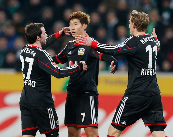 Bayer Leverkusen's Gonzalo Castro, left, and Stefan Kiessling, right sandwich Son Heung-min after his game-deciding goal against Borussia Monchengladbach on Friday.