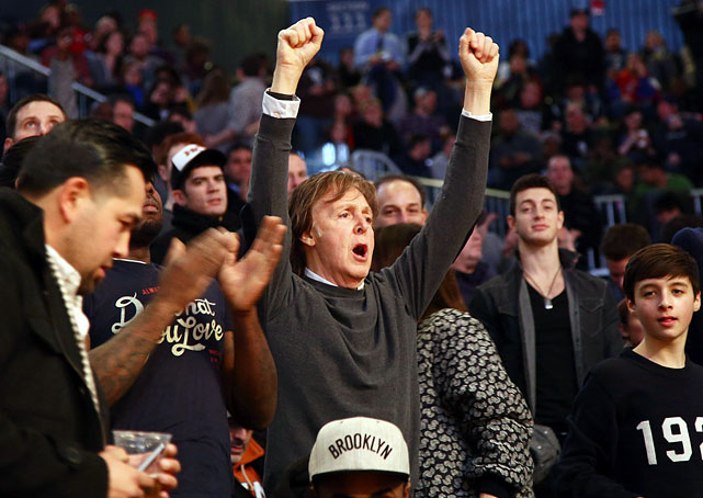 Sir Paul McCartney cheers while watching the Brooklyn Nets play the Philadelphia 76ers during a game at the Barclays Center. He proved no matter how rich and famous you are, nothing beats the prospect of catching a free T-shirt.