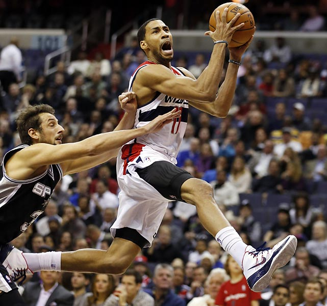 Washington Wizards guard Garrett Temple drives to the hoop as San Antonio Spurs guard Marco Belinelli struggles to keep up. The Wizards fell to the Spurs 118-112 in double overtime.