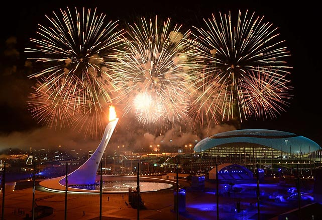 Fireworks explode over Fisht Olympic Stadium during the Opening Ceremony of the 2014 Sochi Games with the Olympic flame lit in the foreground.