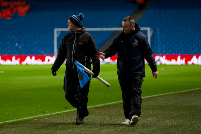 Manchester City groundskeepers pick up the corner flags after Wednesday's match vs. Sunderland was postponed.