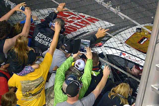 Fans crowd the fence to take pictures of Dale Earnhardt Jr.