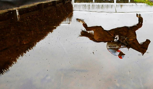 Water displays the reflection of jockey Aidan Coleman as he and Stone Light navigate the Newbury racecourse in England.