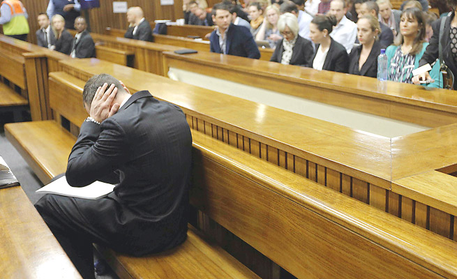 Oscar Pistorius briefly covers his ears while on trial for the murder of his girlfriend, Reeva Steenkamp.