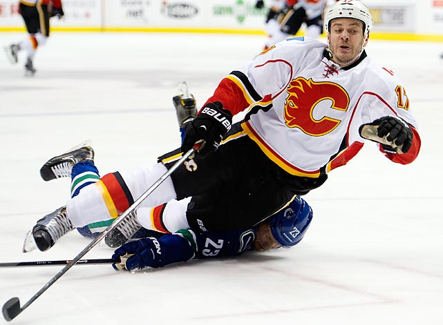 Lance Bouma of the Calgary Flames falls after being tripped by Alexander Edler of the Vancouver Canucks during a Saturday NHL game in Vancouver. The Canucks rallied to win 2-1, snapping a four-game losing streak.