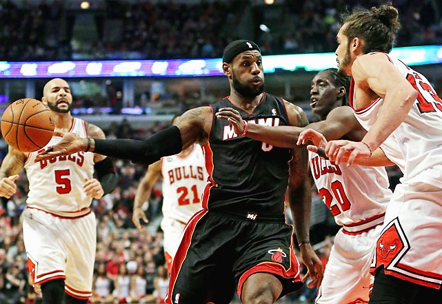 LeBron James attempts a no-look pass as Tony Snell and Joakim Noah of the Chicago Bulls defend in a Sunday game. Chicago ultimately beat the Heat 95-88 in overtime, giving Miami its third consecutive loss.