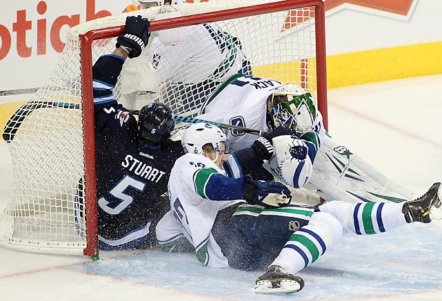 Alexander Edler of the Vancouver Canucks crashes into Mark Stuart of the Winnipeg Jets, who in turn hurls into the net and bashes Vancouver goaltender Eddie Lack. The Canucks won 3-2.