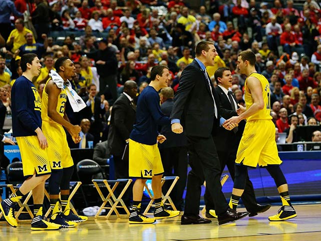 Nik Stauskas, shown here getting congratulations from teammates, sank four of Michigan's 14 3-pointers en route to finishing with 17 points and a career-high eight assists.