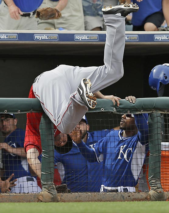 Angels third baseman David Freese tumbles over a dugout railing as he tries to catch a foul ball by Kansas City's Eric Hosmer.