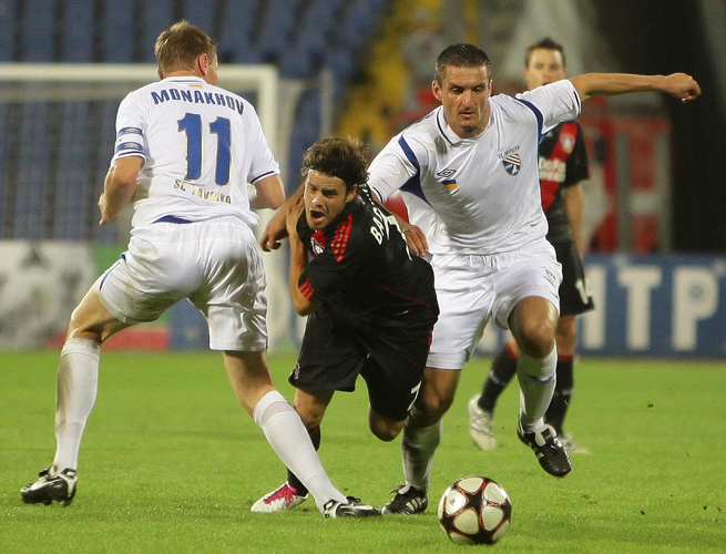 Bayer Leverkusen's Tranquillo Barnetta, center, gets tripped up by Tavriya Simferopol's Anton Monakhov during their UEFA Europa League clash in Simferopol, Ukraine, on Aug. 26, 2010.