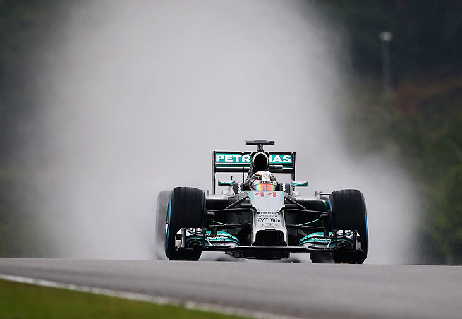 Lewis Hamilton navigated a wet track in Sepang to secure the 33rd pole of his career.