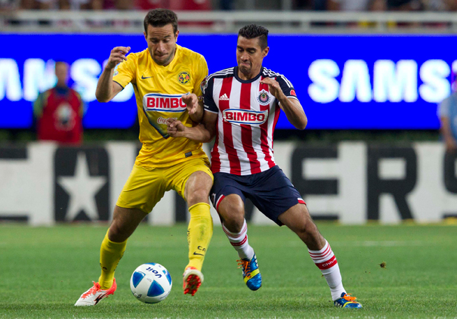 Club America's two-goal scorer Luis Gabriel Rey, left, fights with Chivas' Patricio Araujo for possession in Sunday's rivalry clash.