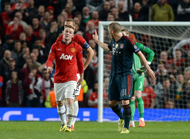 Bastian Schweinsteiger (31) gestures to Wayne Rooney after committing a foul that got him sent off in Bayern Munich's 1-1 Champions League draw with Manchester United.