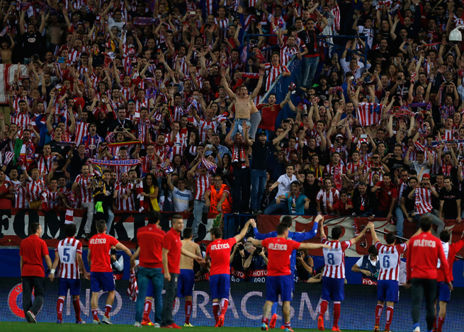 Atletico Madrid players celebrate eliminating Barcelona from the Champions League with their raucous fans at Estadio Vicente Calderon on Wednedsay.