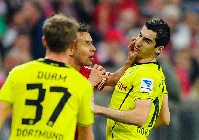 Rafinha, center, was sent off for putting his hands to the face of Dortmund's Henrikh Mkhitaryan and will be forced to sit out Bayern's next three league games.