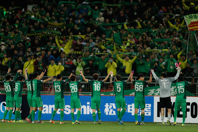 Beijing Guoan players salute their raucous supporters at Beijing Worker's Stadium.